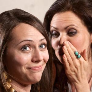 Närbild på två kvinnor, den ena viskar i den andras öra