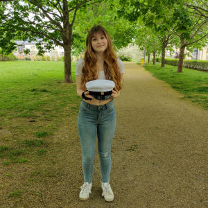 En kvinna står i en park och håller fram en studentmössa.