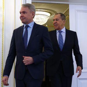 Pekka Haavisto och Sergej Lavrov (i den ordningen) anländer till ett rum genom dubbeldörrar.