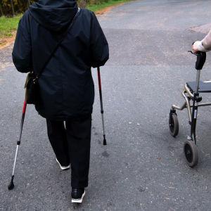 Kaksi vanhusta kävelee ulkona.