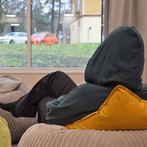 En ung person sitter med en grå munkjacka med huvan dragen över huvudet. Personen har ryggen mot kameran och tittar ut genom ett fönster på en regnig parkeringsplats.