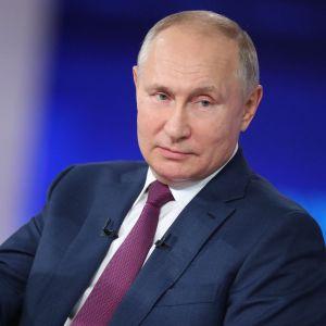 Vladimir Putin i närbild med huvudet på sned och höger handen utsträckt till sidan.