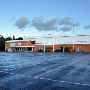 En idrottshall och dess parkering.
