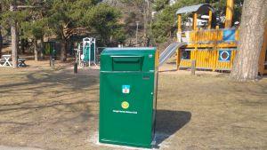 Ett grönt smart sopkärl står invid en lekpark.