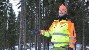 En man i gul rock står i en skog. Han hållerupp ena handen i luften, som om han visar på något medan han talar.