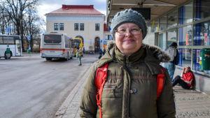 En kvinna står utanför Borgå busstation. Hon tittar in i kameran och ler.