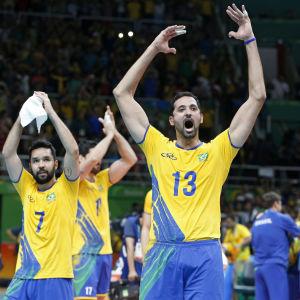 Två gulklädda brasilianska volleybollspelare jublar efter vinst.