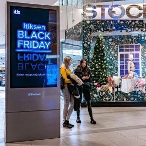 Ihmisiä Stockmannin edessä Black Friday-mainoksen vieressä Itiksessä.
