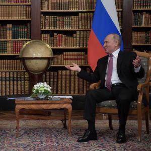 Joe Biden och Vladimir Putin sitter på varsin stol och gestikulerar framför ländernas respektive flaggor.
