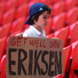 """En pojke håller upp en skylt med texten """"Get well soon Eriksen"""" där han står på läktaren under matchen mellan England och Krotatien."""