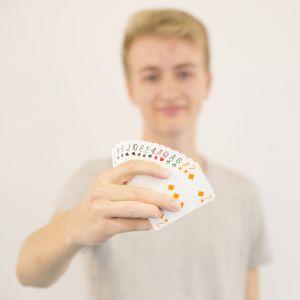 Erik Hansson on ojentanut bridgekäden kameran suuntaan. Kuva on tarkentunut kortteihin.