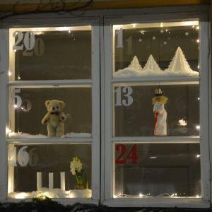 Ett fönster med sex rutor, där varje ruta är en lucka i en julkalender.
