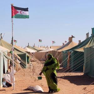 Bild på tältby med kvinna insvept i grön schal i förgrunden.
