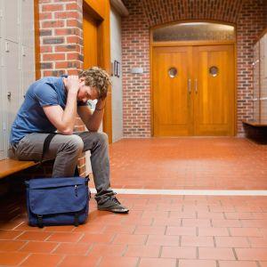 Nedstämd studerande ensam i skolkorridor.