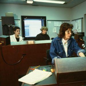 Ohjaaja Rauni Ranta ohjaa radiostudiossa, taustalla äänitarkkailijat.
