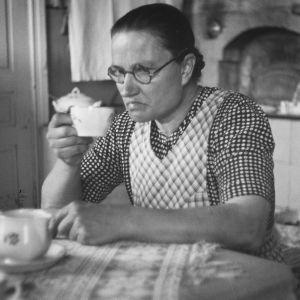 Nainen juo kahvia tuvan pöydän ääressä