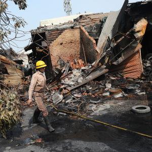 Palomies kulkee mellakoissa tuhoutuneen rakennuksen ohi.