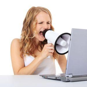 En tjej skriker i en megafon riktad mot en datorskärm.