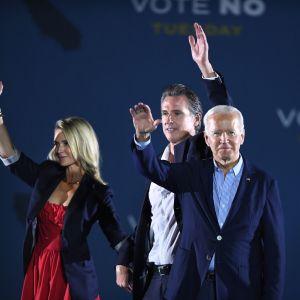 Kuvernööri Gavin Newsome vaimonsa Jennifer Siebel Newsomin sekä presidentti Joe Bidenin kanssa kampanjatilaisuudessa maanantaina Long Beachissä.