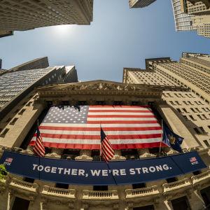 Yhdessä olemme voimakkaita -teksti ja Yhdysvaltain lippu pörssirakennuksen seinällä.