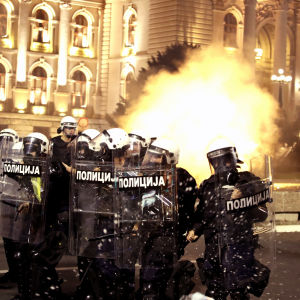 Kravallpoliser i full mundering står framför parlamentet i Belgrad. I bakgrunden syns en explosion av något slag.