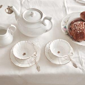 Ett dukat bord med vit bordduk, vit tekanna och vita koppar. Ett blommigt fat med bullar.