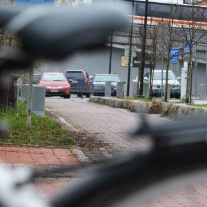 En cykelväg som slutar i en parkeringsplats. I förgrunden en cykel.
