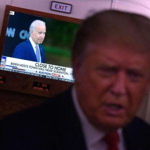 Donald Trump oskarp, med Joe Biden i en tv-ruta bakom honom, ombord på sitt flygplan.