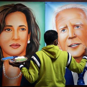 En person gör en väggmålning av Kamala Harris och Joe Biden.