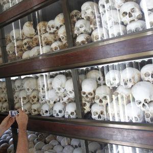 En turist fotograferar kvarlevorna av de som dog under de Röda khmerernas skräckvälde.
