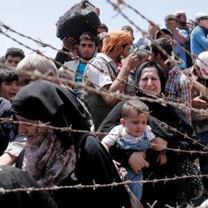 Syriska flyktingar väntar på att släppas in i Turkiet vid gränsen mellan Turkiet och Syrien.