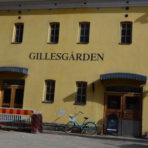 En cykel och en gul byggnad.