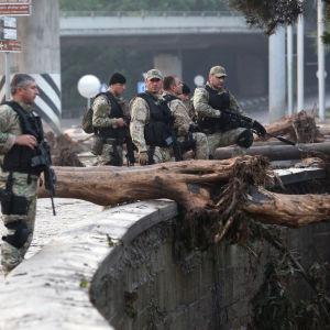 Beväpnad polis partullerar på de översvämmade gatorna i Tbilisi.