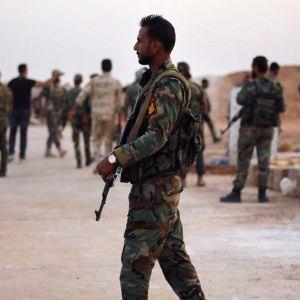 En syrisk soldat spankulerar beväpnad, utan huvudbonad.