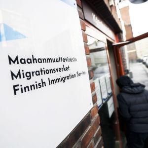 Maahanmuuttoviraston kyltti ja sisäänkäynti.