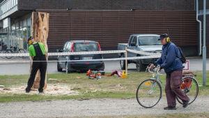 Mies selin kameraan sahaamassa puuveistosta moottorisahalla kuulosuojaimet päässä puistossa. Mies kävelemässä polkupyörän kanssa kuulosuojaimet päässä.