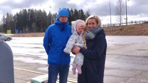 En man, en kvinna och ett barn på en parkeringsplats.