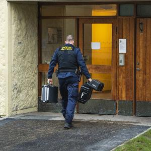 En polisman vid ingången till ett höghus.