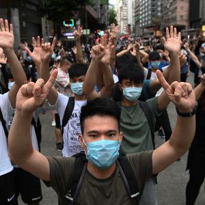 Mielenosoittajia kädet ylhäällä.