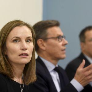 En kvinna stirrar stint mot kameran, i bakgrunden syns två män i kostym suddigt.