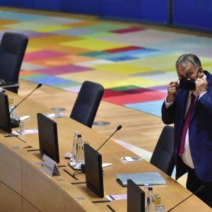 Ungerns premiärminister Viktor Orban står bakom ett mötesbord