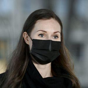 Statsminister Sanna Marin (SDP) i närbild på Ständerhusets trappor i Helsingfors. Hon har ett svart munskydd på sig.
