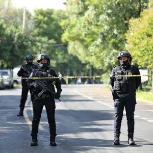 Kolme aseistautunutta poliisia seisoo kadulla vartioimassa eristettyä aluetta. Kauempana näkyy vielä yksi poliisi.