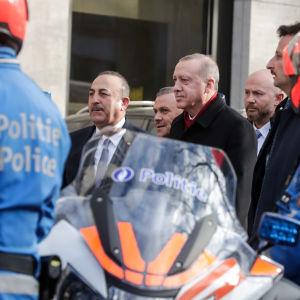 Turkin ulkoministeri ja presidentti kävelevät poliisirivistön ohi Brysselissä.