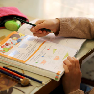 tyttö tekee koulutehtäviä kotona