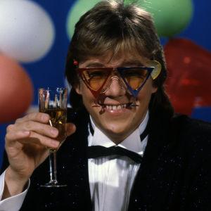Hittimittarin vappuohjelmaa juontava Mikko Alatalo kohottaa maljan päässään kolmionmuotoiset värikkäät silmälasit.