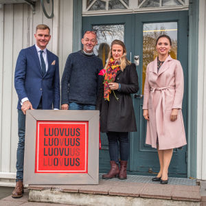 Jouni Eho, Vesa Ristimäki, Netta Norro och Emilia Vesalainen-Pellas står på en trappa och håller i ett konstverk med texten Luovuus.