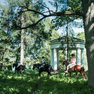Kolme ratsukkoa matkalla metsän halki, ohittavat 1800-lukulaisen huvimajan.