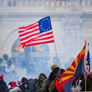USA:s flagga vajar över en folkmassa framför kongressbyggnaden i Washington. Luften är dimmig av tårgas.