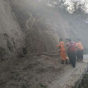 Räddningsarbetare röjer undan bråte på bergsvägar efter jordskalv och jordskred för att på folk som sitter fast på den aktiva vulkanen